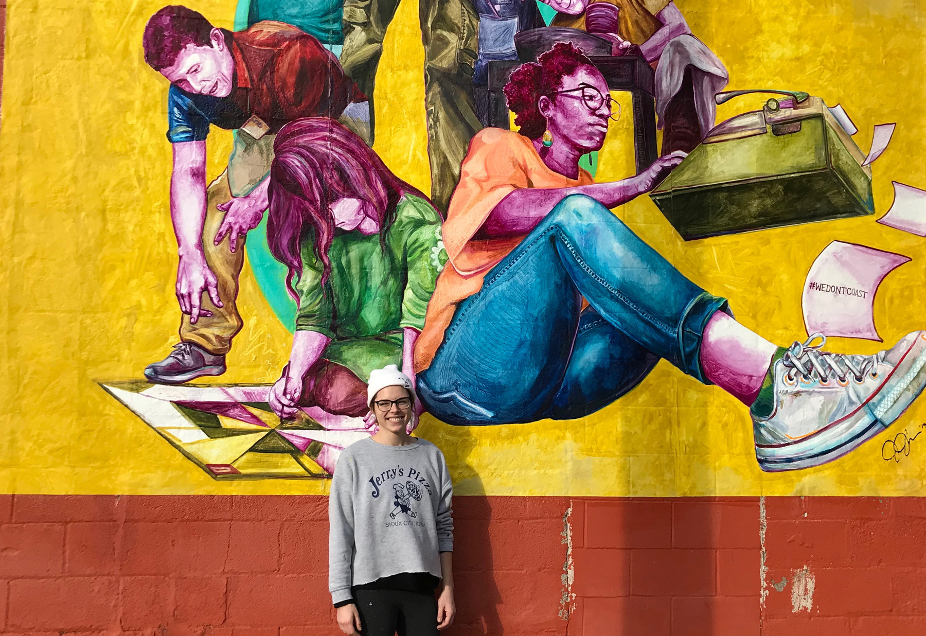Artist Jenna Johnson next to mural